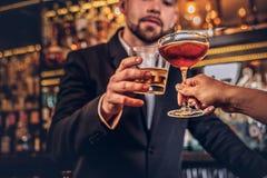 一对有吸引力的夫妇的播种的图象度过在一个浪漫设置的晚上,喝酒在酒吧柜台 免版税库存照片