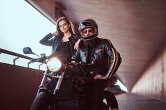 一对有吸引力的夫妇的画象-盔甲的残酷有胡子的骑自行车的人和太阳镜在黑皮夹克穿戴了 库存图片