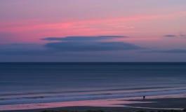 一对浪漫夫妇捉住在一个空的诺森伯兰角海滩的最后光 免版税库存照片