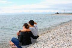 一对浪漫夫妇的后面看法在海滩的在暑假时 库存图片