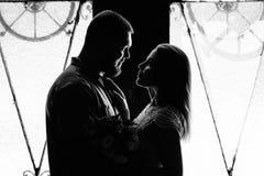 一对浪漫夫妇的画象在背后照明的从窗口或门,一对夫妇的剪影在一个门道入口的与背后照明,夫妇o 免版税库存图片