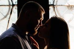 一对浪漫夫妇的画象在背后照明的从窗口或门,一对夫妇的剪影在一个门道入口的与背后照明,夫妇o 免版税图库摄影