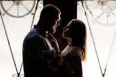 一对浪漫夫妇的画象在背后照明的从窗口或门,一对夫妇的剪影在一个门道入口的与背后照明,夫妇o 免版税库存照片
