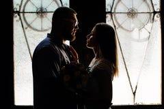 一对浪漫夫妇的画象在背后照明的从窗口或门,一对夫妇的剪影在一个门道入口的与背后照明,夫妇o 库存图片