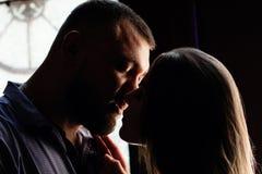 一对浪漫夫妇的画象在背后照明的从窗口或门,一对夫妇的剪影在一个门道入口的与背后照明,夫妇o 图库摄影