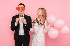 一对爱恋的夫妇、男人拿着在他的眼睛的两纸心脏和拿着一花束,在桃红色背景的妇女 免版税库存图片