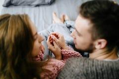 一对爱恋的夫妇互相看和握手,当在家坐在床上一起时 附庸风雅 选择聚焦 免版税库存图片