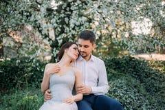 一对爱恋的夫妇在一个开花的庭院里拥抱 一件谦虚,灰色礼服的红发女孩在土气样式 时髦和谨慎 免版税库存照片