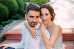 一对爱恋的夫妇在一个开花的庭院里拥抱 一件谦虚,灰色礼服的红发女孩在土气样式 时髦和谨慎 库存照片