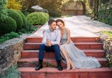一对爱恋的夫妇在一个开花的庭院里拥抱 一件谦虚,灰色礼服的红发女孩在土气样式 时髦和谨慎 图库摄影