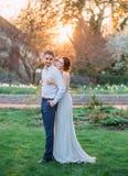 一对爱恋的夫妇在一个开花的庭院里拥抱 一件谦虚,灰色礼服的红发女孩在土气样式 时髦和谨慎 库存图片