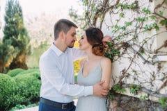 一对爱恋的夫妇在一个开花的庭院里拥抱 一件谦虚,灰色礼服的红发女孩在土气样式 时髦和谨慎 免版税图库摄影