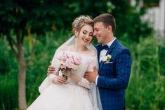一对爱恋的夫妇在一个绿色公园走在他们的婚礼之日 新婚佳偶拥抱并且笑,轻轻地互相接触` s 库存照片
