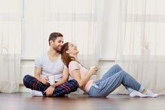 一对爱恋的夫妇在地板上笑反对窗口 图库摄影