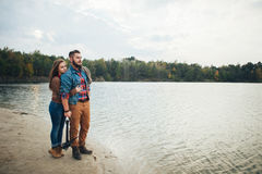 一对爱恋的夫妇在山河的河岸站立,拥抱 免版税库存照片