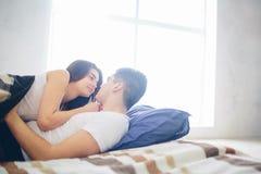 一对爱恋的夫妇在床上说谎 明亮和舒适卧室 家庭舒适和爱 免版税库存照片