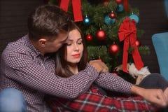 一对爱恋的夫妇在新年` s伊芙的一棵圣诞树附近轻轻地拥抱 免版税库存照片