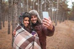 一对爱恋的夫妇在森林,他人做与女孩的selfie 库存图片
