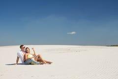 一对爱恋的夫妇在白色沙子说谎 免版税库存照片