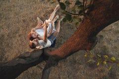 一对爱恋的夫妇坐在树下 免版税库存照片