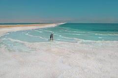 一对爱恋的夫妇基于死海 盐溶海岸线,海在以色列灭绝并且烘干  库存照片