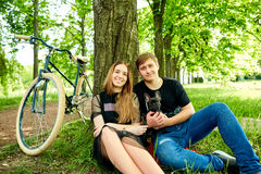 一对爱恋的夫妇由在草的树休息在公园 免版税库存图片