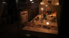 一对爱恋的夫妇由烛光用餐在壁炉附近 股票录像