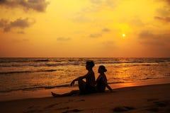一对爱恋的夫妇的剪影在海洋的支持 库存照片