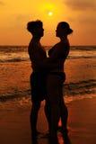 一对爱恋的夫妇的剪影在海洋的支持 免版税库存图片