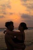 一对爱恋的夫妇的剪影在海洋的支持 免版税库存照片