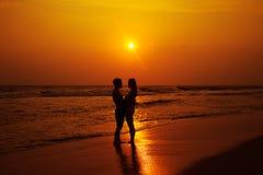 一对爱恋的夫妇的剪影在海洋的支持 库存图片