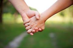 一对爱恋的夫妇的手。友谊的概念 免版税库存图片
