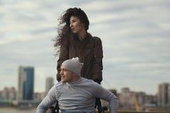 一对爱恋的夫妇的画象-有年轻残疾人的美丽的妇女俯视城市的小山的 免版税图库摄影
