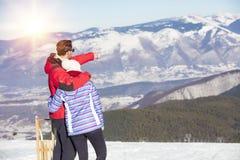 一对爱恋的夫妇的背面图在毛皮看下雪的山脉的敞篷夹克的 免版税库存照片