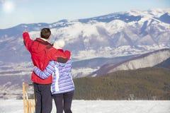 一对爱恋的夫妇的背面图在毛皮看下雪的山脉的敞篷夹克的 库存照片