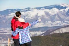 一对爱恋的夫妇的背面图在毛皮看下雪的山脉的敞篷夹克的 图库摄影