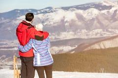 一对爱恋的夫妇的背面图在毛皮看下雪的山脉的敞篷夹克的 库存图片