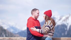 一对站立在山和亲吻背景的年轻可爱的夫妇游人  股票录像