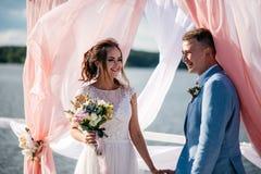 一对美好和愉快的夫妇、新娘和新郎,在码头的立场在婚礼曲拱下 免版税库存图片
