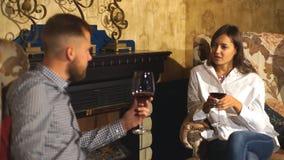 一对美好的夫妇喝酒坐椅子由壁炉 股票录像