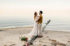 一对美好的夫妇在海背景拥抱 在亲吻前的片刻 在海滩的浪漫日期 婚姻 免版税图库摄影