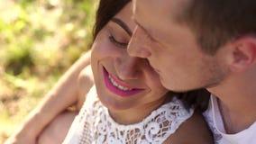 一对美好的年轻夫妇坐草在公园在树附近 股票录像
