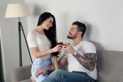 一对美好的年轻夫妇坐长沙发和饮用的酒,他们一起是愉快的 免版税库存照片