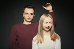 一对美好的年轻夫妇的画象在摆在黑暗的背景的演播室的爱的 库存照片