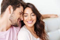 一对美好的微笑的夫妇的特写镜头画象在长沙发的 图库摄影