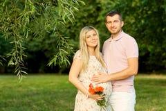 一对美好的怀孕的夫妇的画象在一个夏天停放 免版税库存照片