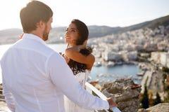 一对美好的正义已婚夫妇的后面看法,佩带在白色衣物,有城市后面全景的,婚礼在希腊 免版税库存照片