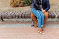 一对美好的年轻愉快的夫妇的腿在走通过握手的城市的街道和公园的爱的 免版税库存图片