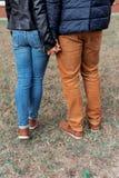 一对美好的年轻愉快的夫妇的腿在走通过握手的城市的街道和公园的爱的 库存图片
