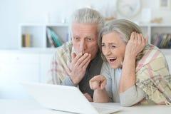 一对资深夫妇的特写镜头画象使用膝上型计算机的 免版税库存照片